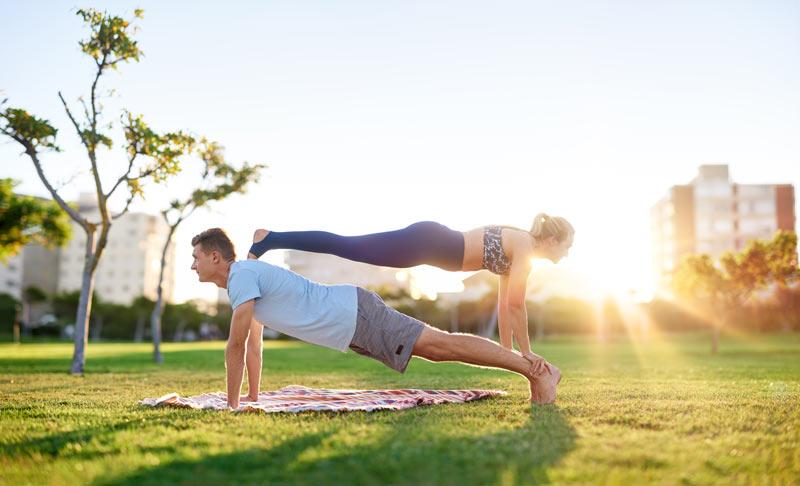 Couple effectuant une figure d'acroyoga dans un parc urbain