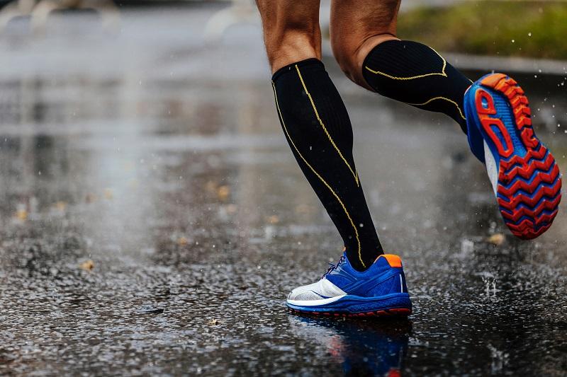 homme qui court avec des chaussettes de compression